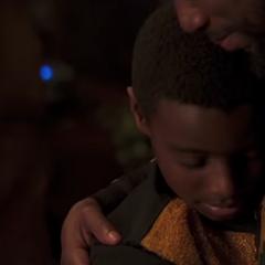 T'Challa es abrazado cariñosamente por su padre.
