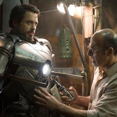 Stark es ayudado por Yinsen a colocarse la armadura.