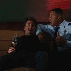 Stark y Rhodes toman licor en el avión privado.