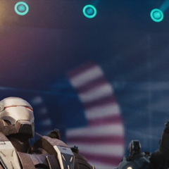 La armadura de Rhodes comienza a atacar a Stark.