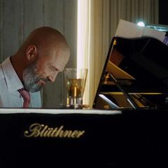 Stane toca el piano mientras espera a Stark.