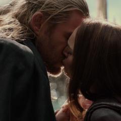 Foster y Thor se besan en la orilla de un lago.