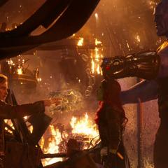 Gamora es tomada de rehén por Thanos mientras Quill le apunta su bláster.