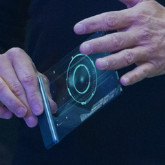 Tony Stark holding a J.A.R.V.I.S. mobile device while working with <a href=