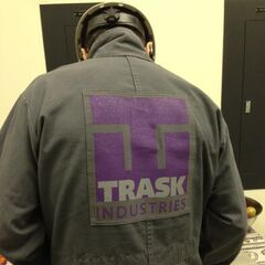 A man wearing a Trask Industries uniform spotted on set.
