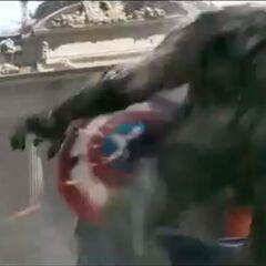 Captain America attacks with his shield.