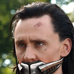 Loki, muzzled and chained after being defeated, but before returning with Thor to Asgard.