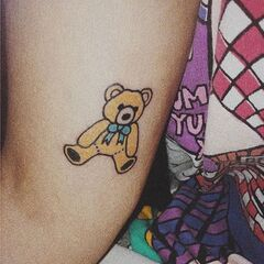 Melanie Martinez got this tattoo of a yellow teddy bear on her arm in September 2014.