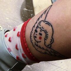 Melanie Martinez has a tattoo on her ankle of an angel with a retro pin-up style head. All of the tattoo is a black outline except for the rosy cheeks.