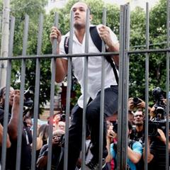 Rapaz tenta pular o portão