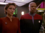 Kira Nerys and Benjamin Sisko listen to Akorem Laan