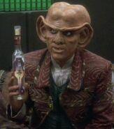 Quark holding Aldebaran whiskey bottle