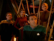 O'Brien, Kira, Bashir, and Odo listen to Kor