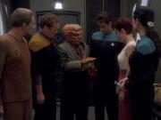 Quark überreicht Kira eine Flasche Likör