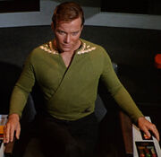 Kirk wearing green wraparound tunic, collar rank