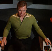 Kirk wearing green wraparound tunic, collar rank
