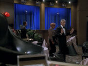 Vic führt Bashir und Quark durch die zerstörte Lounge