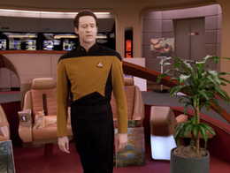 Spot sitting in captain's chair behind Data