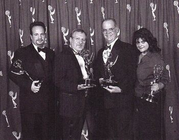 """...winning (l) his 2002 Emmy Award with colleagues (l-r) <a href=""""/wiki/Dan_Curry"""" title=""""Dan Curry"""">Dan Curry</a>, <a href=""""/wiki/Ronald_B._Moore"""" title=""""Ronald B. Moore"""">Ronald B. Moore</a> and <a href=""""/wiki/Elizabeth_Castro"""" title=""""Elizabeth Castro"""">Elizabeth Castro</a>"""