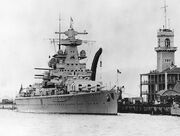 Black-and-white photograph of heavy cruiser Admiral Scheer moored at dock.