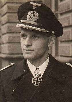 The head and shoulders of a young man, shown in semi-profile. He wears a peaked cap and black naval coat, a white shirt with an Iron Cross displayed at the front of his shirt collar. His facial expression is a determined and confident smile; his eyes gaze into the distance to the left.