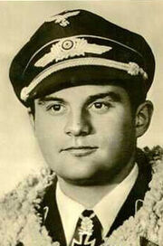 The head and shoulders of a young man, shown in semi-profile. He wears a peaked cap and a pilot's leather jacket with a fur collar, with an Iron Cross displayed at the front of his shirt collar. His nose is long and straight, and his facial expression is a determined and confident smile; his eyes gaze into the distance.
