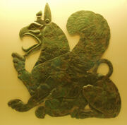 Placa que representa un animal mitad león mitad águila, sentado con el pico abierto.