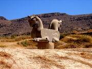 La foto muestra una escultura con dos cabezas de rapaces pegadas espalda a espalda y patas anteriores de león.