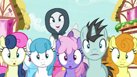Cloaked Rarity appears over crowd of ponies S7E19