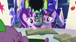 Starlight and Twilight look at each other while holding book S5E26