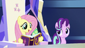 Fluttershy with a copy of the friendship journal S7E14.png