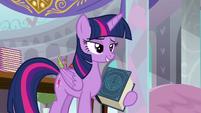 Twilight Sparkle holding the EEA's guidebook S8E1