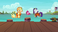 AJ, Pinkie, and Rarity a few feet away from the docks S6E22