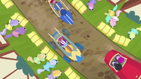 Overhead view of carts racing around a bend S6E14