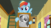 Rainbow smiling with picture of herself S8E20