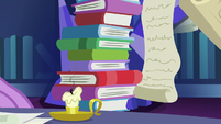 Tall stack of books and a burnt-out candle S7E25