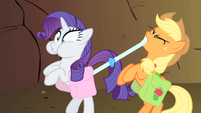 Applejack tightening Rarity's bags S1E21