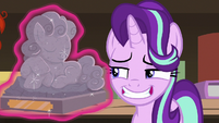 Starlight grinning disinterestedly at pony statuette S7E24
