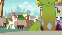 Coco Crusoe and Rainbow Stars approach a table S7E15