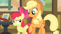 Apple Bloom pushes Applejack away from the quill S4E09