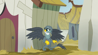 Gabby standing behind a Griffonstone house S6E19