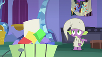 Spike looks at brochure in the trash S9E19