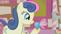 Sweetie Drops looks holds a parasprite in her hoof S1E10