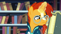 Sunburst closely reading a spell book S7E1