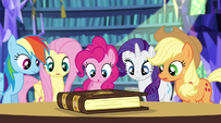 Twilight's friends looking at the storybook EG2