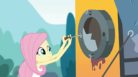 Fluttershy unscrewing the bus's rear window SS13