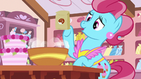 Mrs. Cake tossing sugar into a bowl S7E13