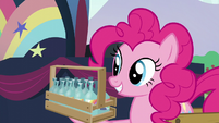 Pinkie shows a holder holding glass containers full of imported water S5E24