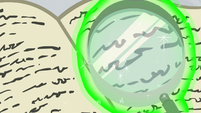 Magnifying glass peering over book text S8E16