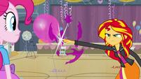 Sunset pops balloon with her finger EG